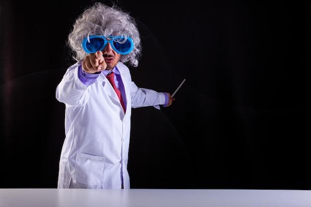 Злой учитель естествознания в белом халате с взлохмаченными волосами в забавных очках указывает пальцем на черном фоне