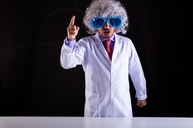 Злой учитель естествознания в белом халате с взлохмаченными волосами в забавных очках с поднятым пальцем