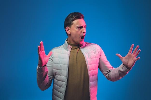 怒りの叫び。ピンクのネオンの光で青い壁に分離された白人男性の肖像画。カジュアルで美しい男性モデル。人間の感情の概念、顔の表情のコピースペース。