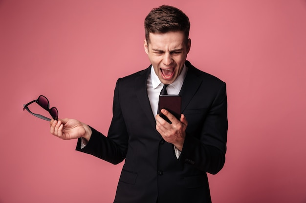Angry screaming displeased young businessman talking by phone