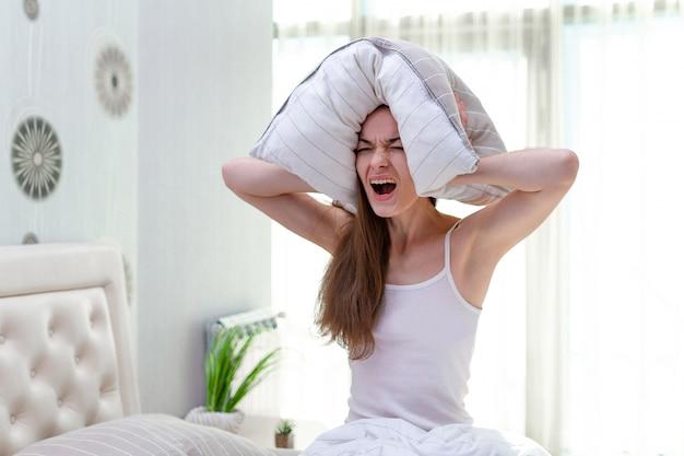 騒々しい隣人に苦しみ、邪魔され、枕で耳を覆うと、早朝に自宅のベッドで眠りに落ちようとする怒って叫んでいる女性
