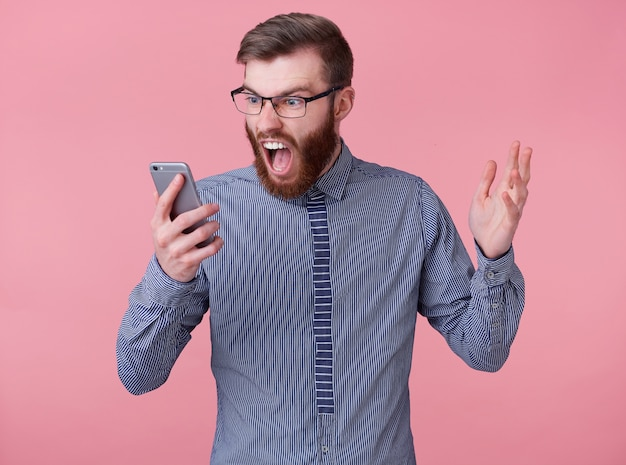 Angry screaming young handsome red bearded man with glasses and a striped shirt, swears with contractors on video chat for work done, stands over pink background.