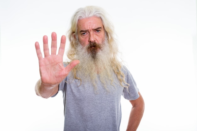 Angry senior bearded man showing stop hand sign