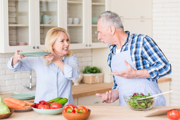 An angry senior couple fighting with each other in the kitchen