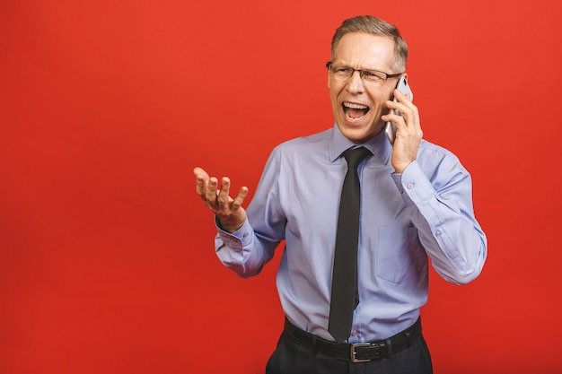 Angry senior man talking on mobile phone isolated on red wall. negative emotions.