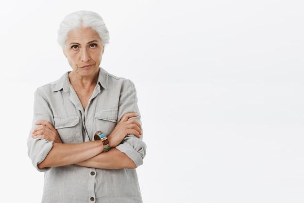 Сердитая старшая женщина выглядит безумной и разочарованной, скрестив руки на груди и хмурится расстроенной