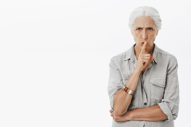 Angry serious granny scolding, shushing, tell be quiet