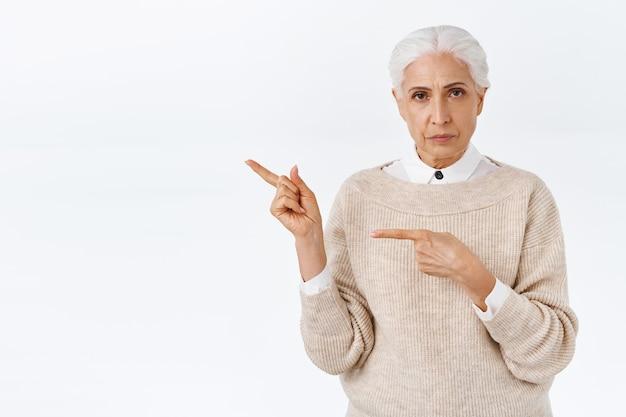 회색 빗질 머리를 가진 화나고 진지하고 엄격하고 우아한 일하는 노부인, 인상을 찌푸린 찡그린 요구 설명, 나쁘고 혼란스러운 것을 손가락으로 가리키는 흰색 벽