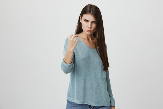 Angry serious woman threaten or scolding someone with fist
