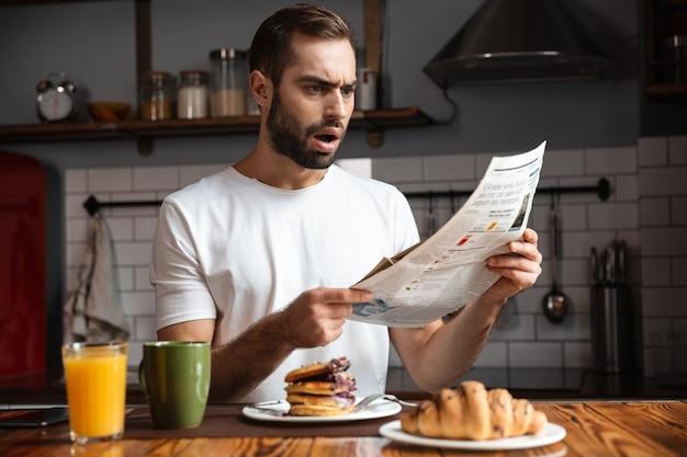 Злой шокированный мужчина завтракает, читает газету