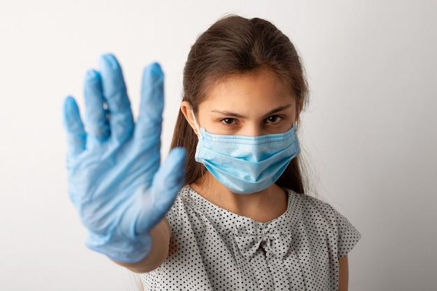 Сердитая маленькая девочка в медицинской маске и перчатках показывает символ остановки