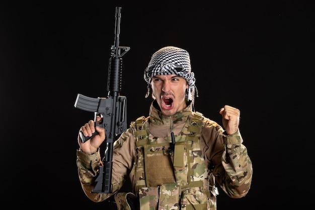 Soldato arrabbiato in mimetica che tiene mitragliatrice sul muro nero