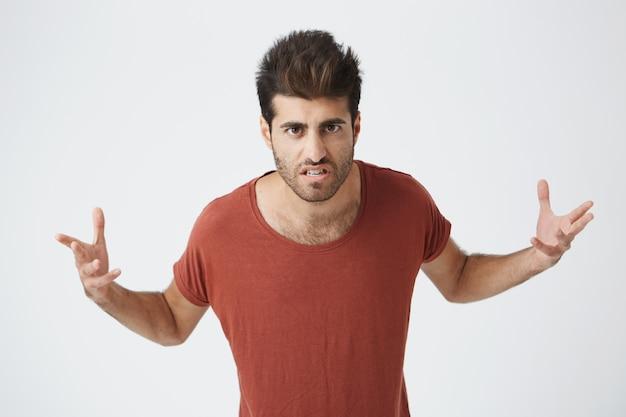イライラした表情が路上で男と戦う準備ができて、手をつないで赤いシャツを着て怒っているスペイン人。ボディランゲージ