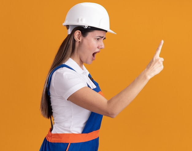 Злой стоя в профиль молодой женщины-строителя в униформе, протягивая палец сбоку, изолированную на оранжевой стене