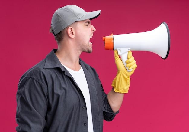 Arrabbiato in piedi in vista di profilo giovane bel ragazzo delle pulizie che indossa t-shirt e berretto con guanti parla su altoparlante isolato sulla parete rosa