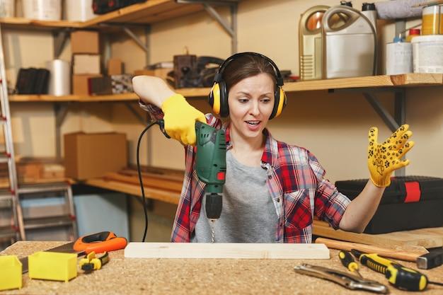 怒ったストレスは、格子縞のシャツを着た若い茶色の髪の女性、テーブルの場所で大工のワークショップで働いているノイズ絶縁ヘッドフォン、木片に電動ドリル穴を開けて、家具を作っています。