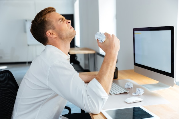 Angry stressed young businessman sitting and crumpling paper in office