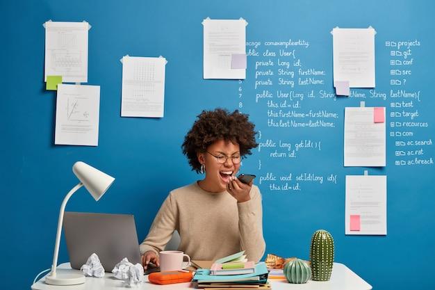 화난 학생 또는 프리랜서 작업자가 전화 통화 중에 화를 내고 노트북 컴퓨터 앞에 앉아 고객과 성가신 대화를 나누며 웹 사이트 용 플랫폼을 개발합니다.