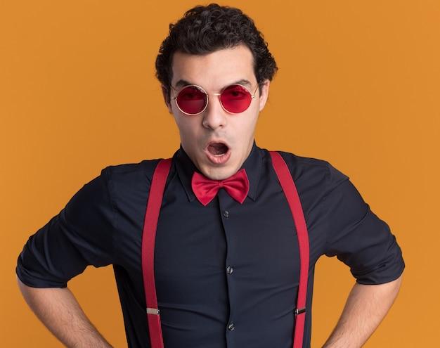 안경과 멜빵을 착용하는 나비 넥타이로 화난 세련된 남자가 오렌지 벽 위에 서서 불쾌 해하는 정면을보고