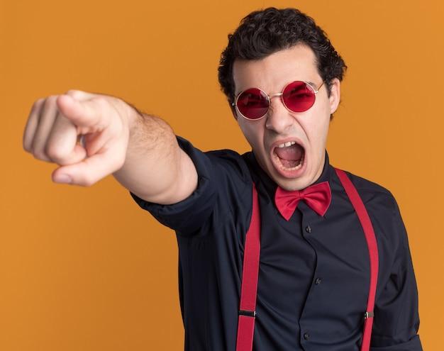 Сердитый стильный мужчина с галстуком-бабочкой в очках и подтяжках кричит с агрессивным выражением лица, указывая указательным пальцем на что-то, стоящее над оранжевой стеной