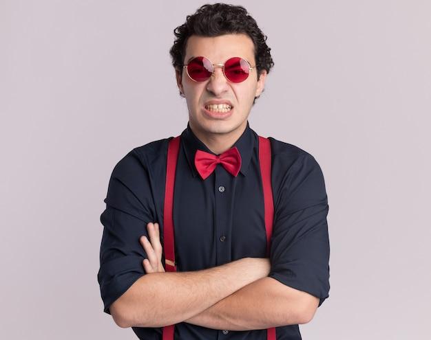 Uomo alla moda arrabbiato con farfallino con gli occhiali e bretelle guardando la parte anteriore con le braccia incrociate in piedi sopra il muro bianco