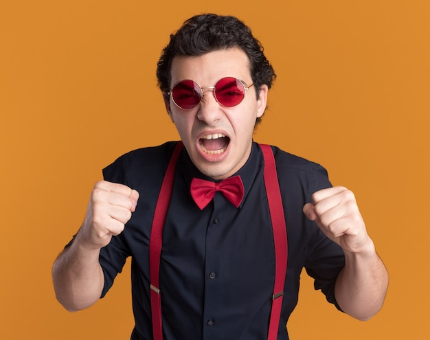 Uomo alla moda arrabbiato con farfallino con gli occhiali e bretelle che grida pugni di serraggio pazzo pazzo in piedi sopra la parete arancione