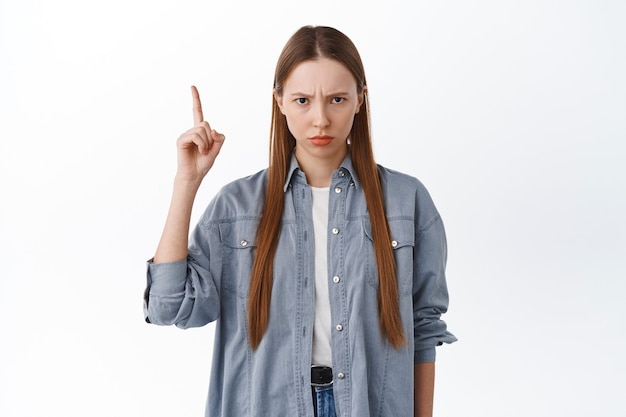 Angry sulking girl frowning, pointing up at unfair thing, being jealous or upset, complaining, standing disappointed against white background.