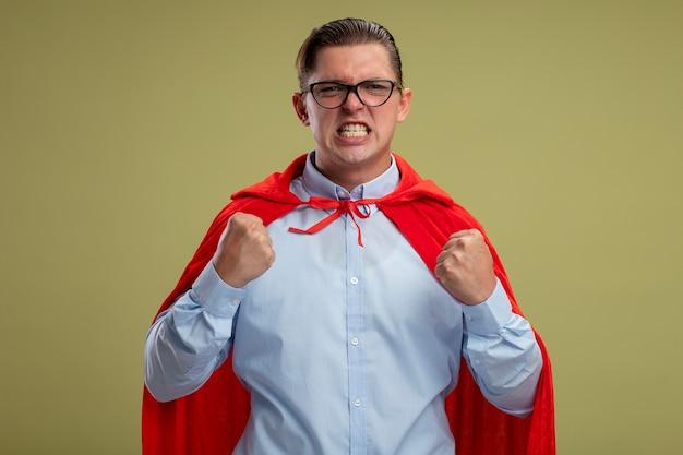Злой супергерой бизнесмен в красной накидке и очках, сжимая кулаки с агрессивным выражением лица, стоя на светлом фоне