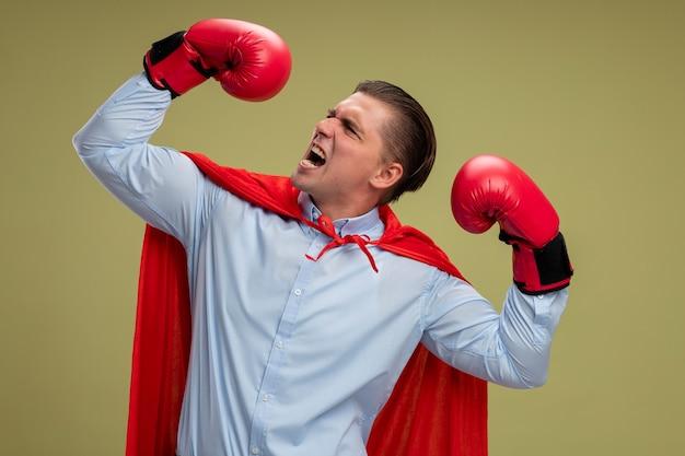 赤いマントとボクシンググローブで怒っているスーパーヒーローの実業家は、明るい背景の上に立っている強さと勇気を示す手を上げます
