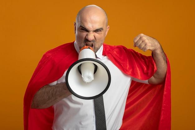 Злой супергерой бизнесмен в красном плаще кричит в мегафон, сжимая кулак, стоя над оранжевой стеной