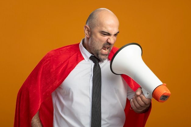 オレンジ色の壁の上に立っているメガホンに叫んでいる赤いマントの怒っているスーパーヒーローの実業家