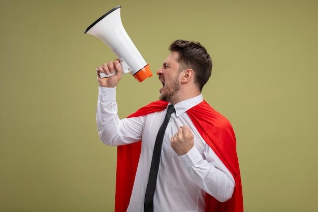 緑の背景の上に立っている攻撃的な握りこぶしでメガホンに叫んで赤いマントの怒っているスーパーヒーローの実業家