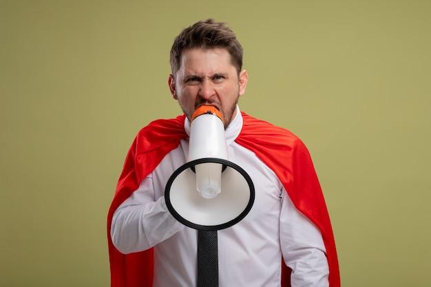 緑の背景の上に立っている攻撃的な表情でメガホンに叫んで赤いマントの怒っているスーパーヒーローの実業家
