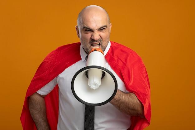 オレンジ色の壁の上に立っている攻撃的な表情でメガホンに叫んでいる赤いマントの怒っているスーパーヒーローの実業家