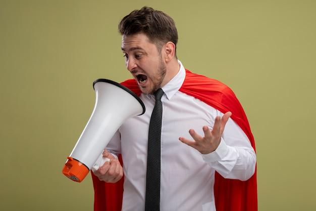緑の背景の上に立っている腕で攻撃的な表情でメガホンに叫んでいる赤いマントの怒っているスーパーヒーローの実業家