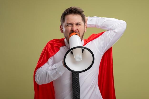 Сердитый бизнесмен супергероя в красном плаще кричит в мегафон с агрессивным выражением лица с поднятой рукой, стоящей на зеленом фоне