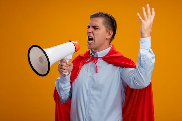 Злой супергерой бизнесмен в красном плаще кричит в мегафон с агрессивным выражением лица с поднятой рукой, стоящей на оранжевом фоне