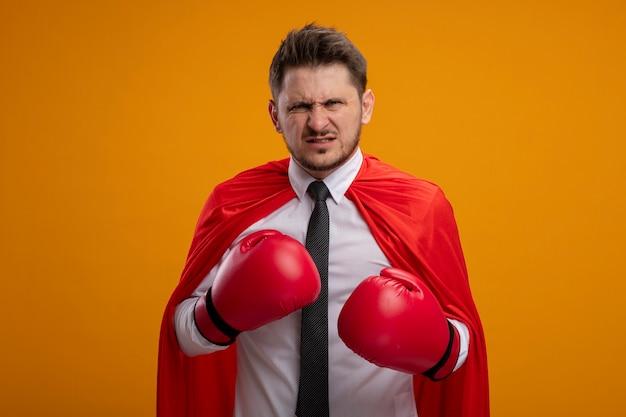 Uomo d'affari arrabbiato super eroe in mantello rosso e guantoni da boxe che guarda l'obbiettivo con espressione aggressiva pronta a combattere in piedi su sfondo arancione