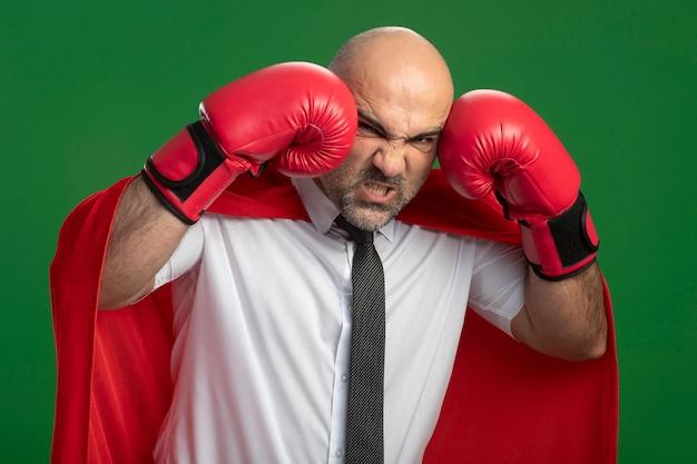 Uomo d'affari arrabbiato super eroe in mantello rosso e guantoni da boxe che si pugni facendo smorfia in piedi sopra la parete verde