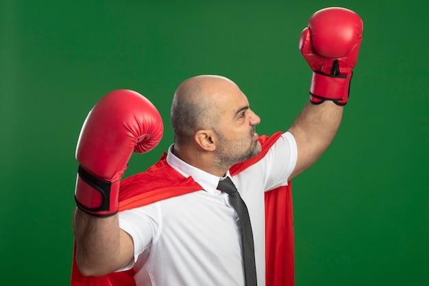 Uomo d'affari arrabbiato super eroe in mantello rosso e guantoni da boxe alzando le mani mostrando il concetto di vincitore di forza e coraggio in piedi sopra la parete verde
