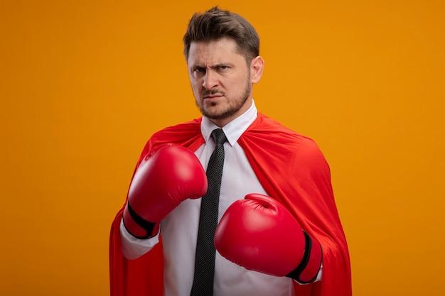 Uomo d'affari arrabbiato super eroe in mantello rosso e guantoni da boxe con espressione aggressiva pronto a combattere in piedi sopra il muro arancione