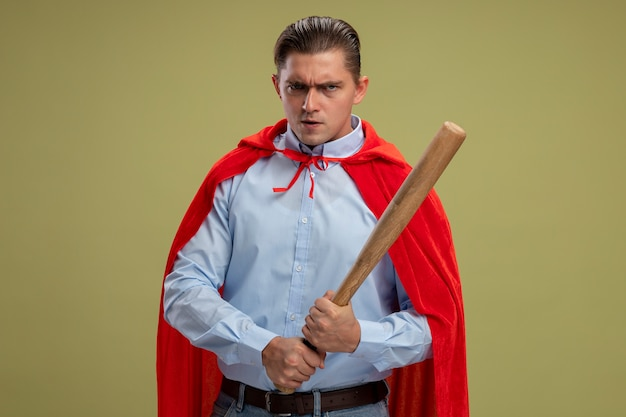 Angry super hero businessman in red cape holding baseball bat looking at camera with serious confident expression standing over light background