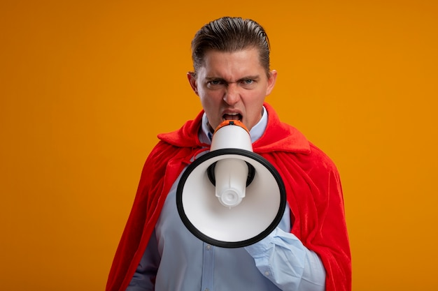 Angry super hero businessman in red cape shouting to megaphone with aggressive expression standing over orange wall