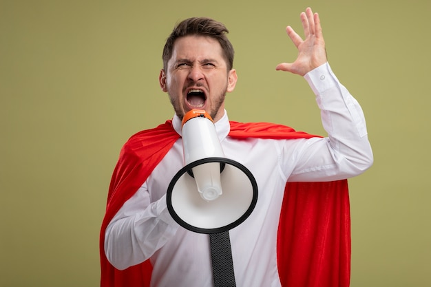 Angry super hero businessman in red cape shouting to megaphone with aggressive expression with raised arm standing over green background