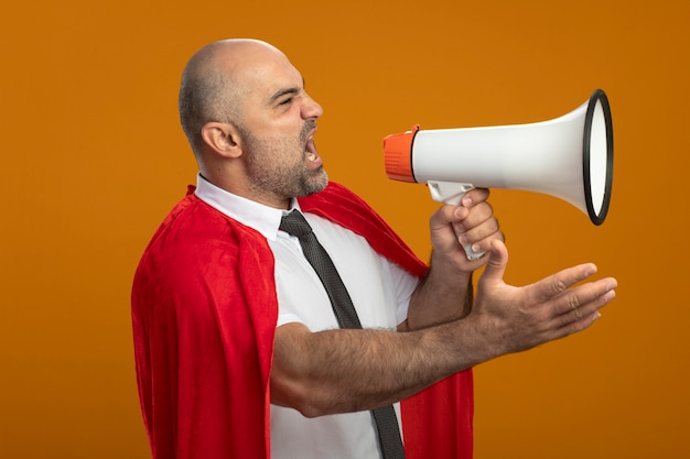Angry super hero businessman in red cape shouting to megaphone with arm out standing over orange wall