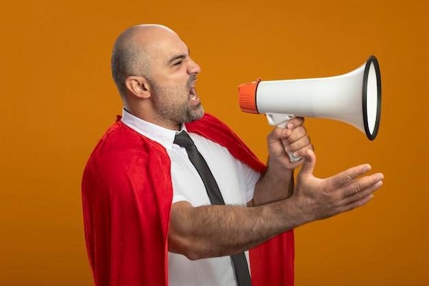Uomo d'affari arrabbiato super eroe in mantello rosso che grida al megafono con il braccio fuori in piedi sopra la parete arancione