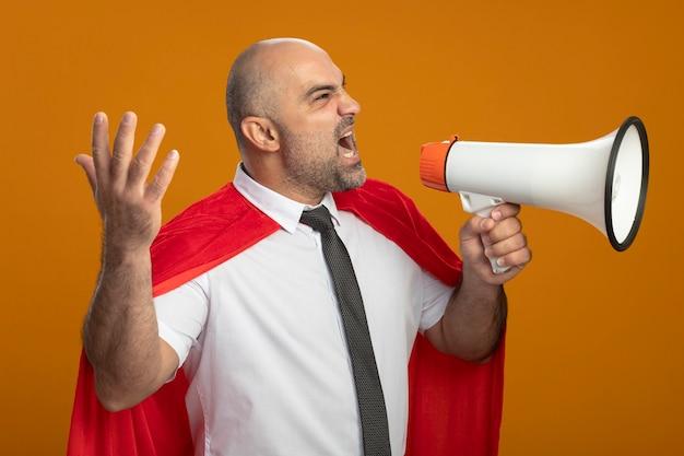 Uomo d'affari arrabbiato super eroe in mantello rosso che grida al megafono con il braccio alzato in piedi sopra la parete arancione