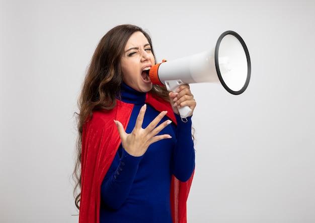 赤いマントを持った怒っているスーパーウーマンが白い壁に隔離されたスピーカーに叫ぶ