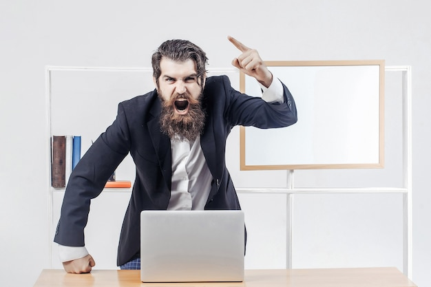 Angry teacher or professor in black suit shouts raised his finger up standing near desk with laptop