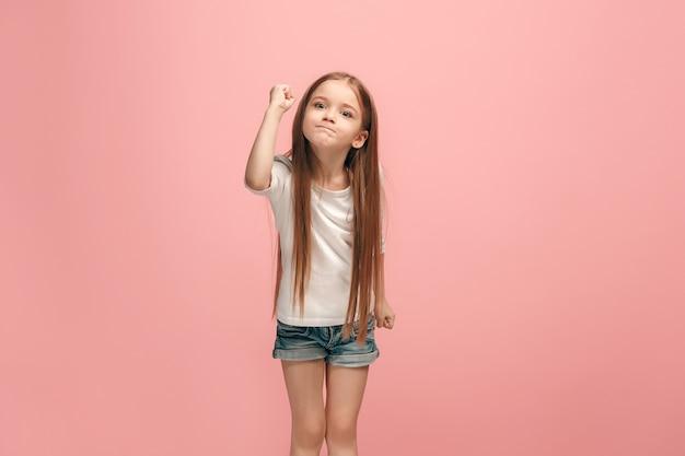 トレンディな青の上に立っている怒っている十代の少女。女性の半身像。人間の感情、表情の概念
